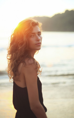 improbable: Portrait of a young beautiful woman with long curly hair at the seaside under the evening sunset