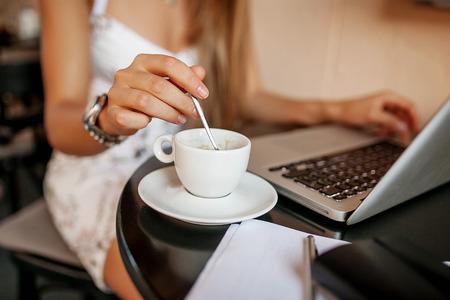 カフェ紅茶コーヒー ノートやメモを取ると wortking を飲む若いビジネス ・ ウーマン