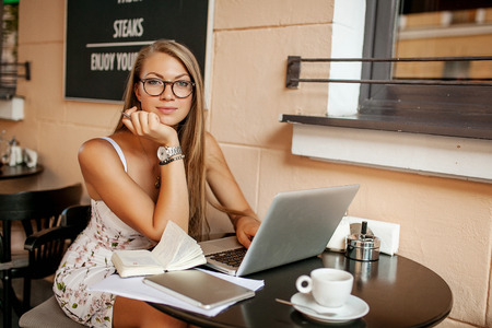 working dress: Young business woman in cafe drinking tea  coffee wortking with laptop and taking notes