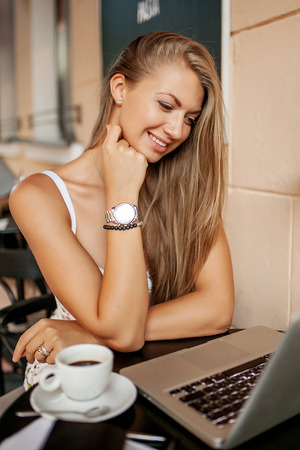Giovane donna d'affari in caffè bere caffè tè wortking con il computer portatile e prendere appunti Archivio Fotografico - 39307058