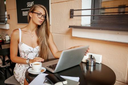 Jonge zakenvrouw in cafe koffie thee koffie wortking met laptop en notities