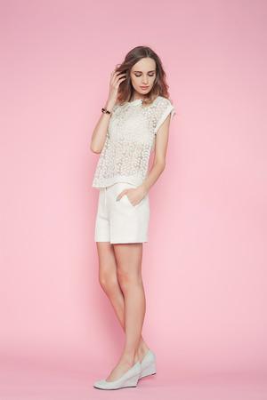 Mooie vrouw in witte kleren poseren op roze achtergrond