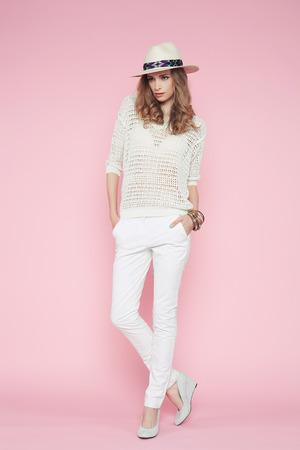 ropa de verano: Mujer hermosa en la ropa blanca que presenta en el fondo de color rosa