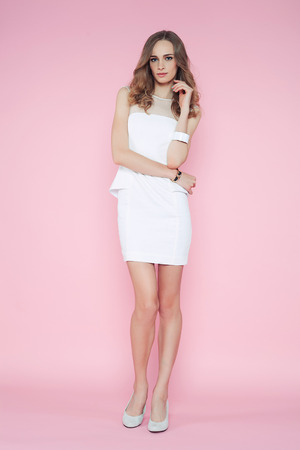 pink posing: Beautiful woman in white clothes posing on pink background