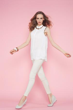 Mujer hermosa en la ropa blanca que presenta en el fondo de color rosa Foto de archivo - 39307064