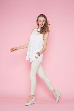 白い服を着て、ピンクの背景のポーズで美しい女性