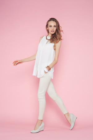 Beautiful woman in white clothes posing on pink background