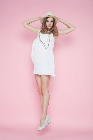 flying woman: Beautiful woman in white dress posing on pink background in hat