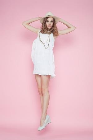 Schöne Frau im weißen Kleid posiert auf rosa Hintergrund in Hut Standard-Bild - 39307074