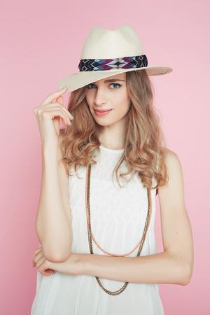 Mooie vrouw in witte jurk poseren op roze achtergrond in de hoed Stockfoto