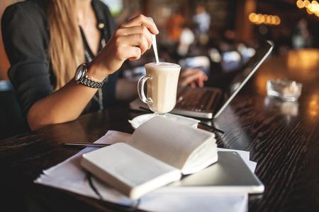 Mujer de negocios en vidrios interiores con café y toma de notas portátil en restaurante Foto de archivo - 39307111