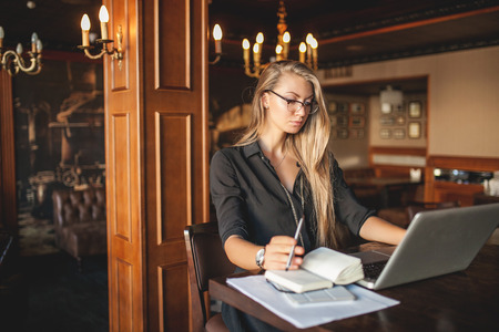 Zakelijke vrouw in glazen binnenshuis met koffie en laptop maken van aantekeningen in restaurant