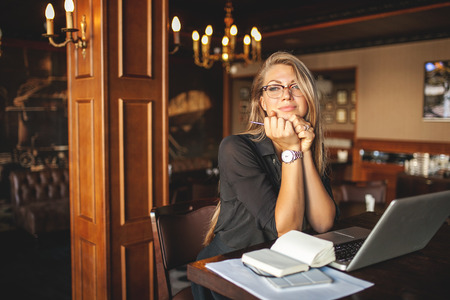 Business woman in glasses indoor with coffee and laptop taking notes in restaurant Stok Fotoğraf - 39307113