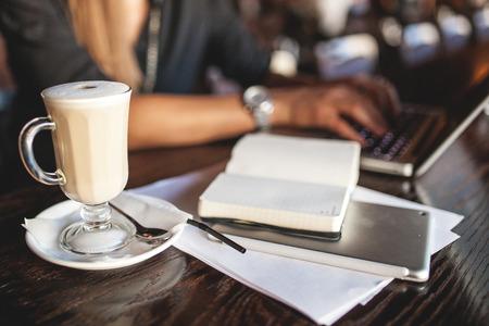 Mujer de negocios en vidrios interiores con café y toma de notas portátil en restaurante Foto de archivo - 39307120