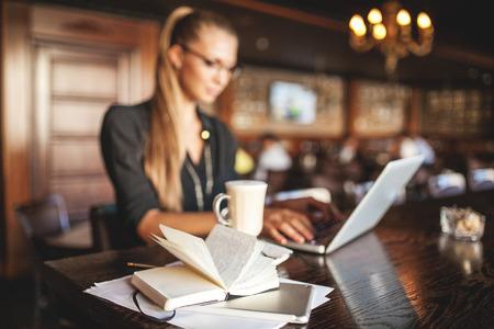 Mujer de negocios en vidrios interiores con café y toma de notas portátil en restaurante Foto de archivo - 39307121