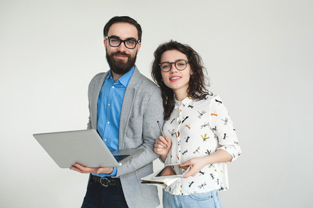 Young hipster man and woman in glasses with laptop and tablet isolated on the blank white background photo