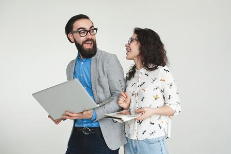 Jonge hipster man en vrouw in glazen met laptop en tablet geïsoleerd op de lege witte achtergrond