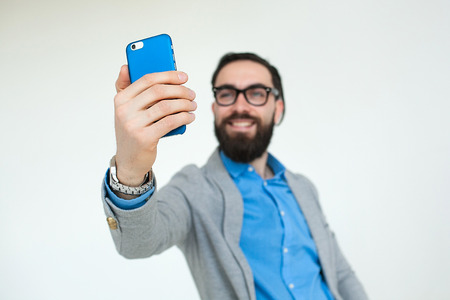 Young hipster with beard in glasses taking selfie and smiling isolated on the blank white background photo