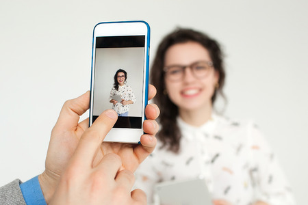 Hand with smartphone taking picture of young woman in glasses with tablet isolated on the blank white background photo