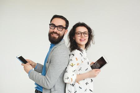 Jonge hipster man en vrouw in glazen met smartphone en tablet die op de lege witte achtergrond