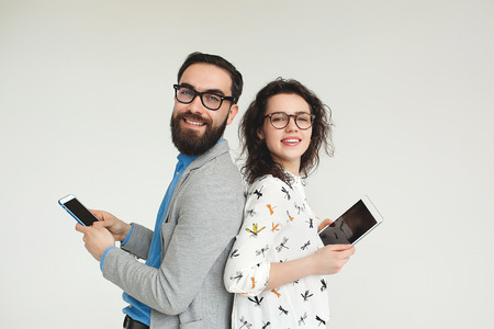 Young hipster man and woman in glasses with smartphone and tablet isolated on the blank white background Фото со стока
