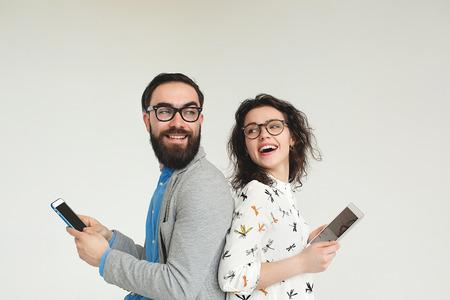 Hombre inconformista joven y mujer en vidrios con el smartphone y la tableta aislado en el fondo blanco en blanco Foto de archivo - 39275689