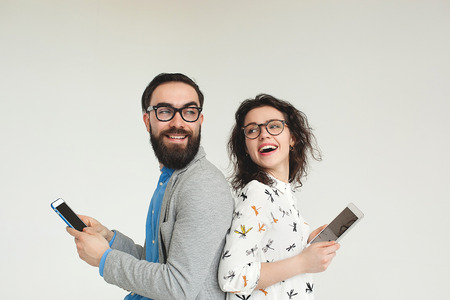 people on phone: Young hipster man and woman in glasses with smartphone and tablet isolated on the blank white background Stock Photo