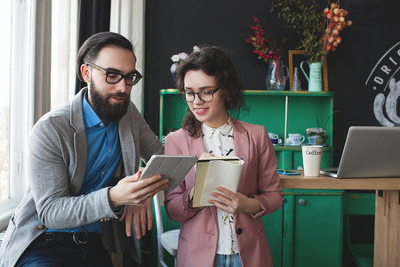 Young hipster man with woman in glasses collaborating in cafe using tablet and notepad Stockfoto