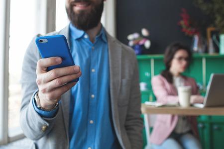 グラス背景上のラップトップに取り組んでいる女性をスマート フォンで青年実業家