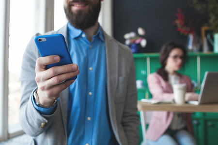 Young businessman in glasses with smartphone over woman working on laptop on background