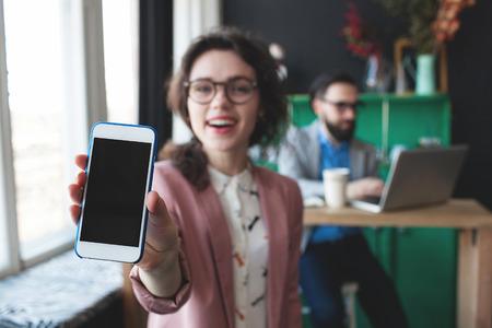 Jonge vrouw in glazen toont smartphone en jonge man aan het werk op de achtergrond