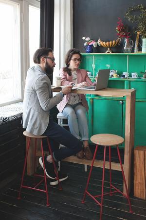 hombres trabajando: Hombre joven inconformista con la mujer en gafas de colaborar en el caf� utilizando tel�fono inteligente tableta del ordenador port�til y el caf� Foto de archivo