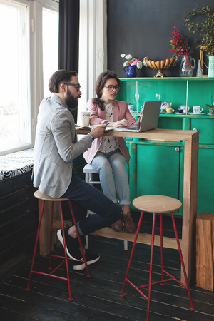 busy beard: Young hipster man with woman in glasses collaborating in cafe using laptop tablet smartphone and coffee Stock Photo