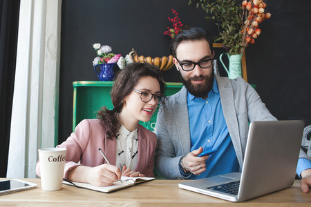 Young hipster man with woman in glasses collaborating in cafe using laptop tablet smartphone and coffee Stockfoto