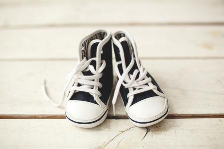 나무 바닥에 아기 검은 색과 흰색 미니 운동화