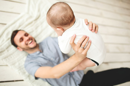 Pareja feliz celebración de padre e hijo en manos acostado en el piso de madera rústica Foto de archivo - 39343439