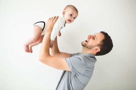 Jonge gelukkige vader bedrijf baby zoon in de handen boven zijn hoofd met geïsoleerde Stockfoto