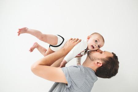 격리 된 배경으로 그의 머리 위로 손에 아기 아들을 들고 젊은 해피 아버지 스톡 콘텐츠 - 39343473