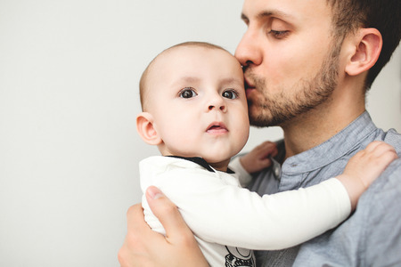 Young happy father kissing baby in hands and smile with isolated background