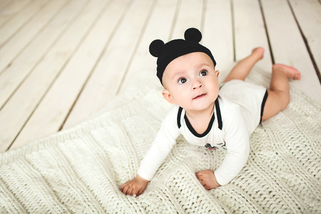 Small cute baby boy in toddler and mouse hat on rustic wooden floor Standard-Bild