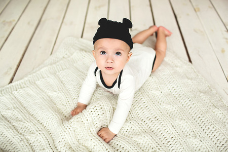 kiddy: Small cute baby boy in toddler and mouse hat on rustic wooden floor Stock Photo