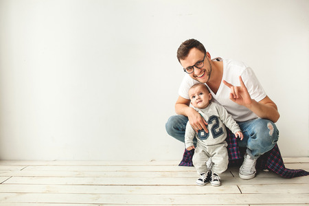 Young hipster father and cute baby boy sitting on rustic wooden floor over white  Stock Photo