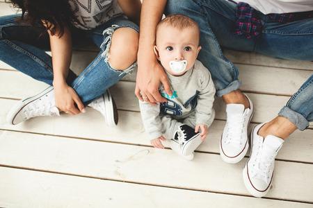 流行に敏感な若いお父さんお母さんと白い背景上素朴な木の床に座っているかわいい赤ちゃん男の子