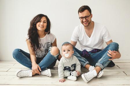 流行に敏感な若いお父さんお母さんと白で素朴な木製の床に座っているかわいい赤ちゃん男の子 写真素材