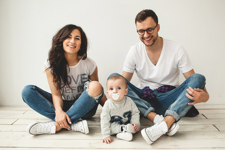 kiddy: Young hipster father mother and cute baby boy sitting on rustic wooden floor over white