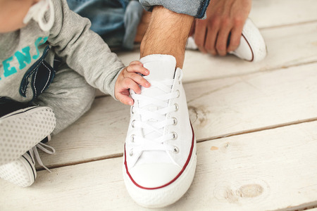wooden shoes: Baby hand on white shoe of the father closeup