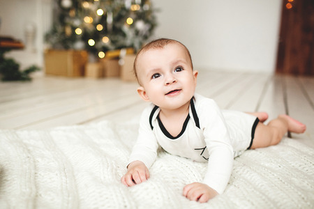 Small cute baby boy in toddler on the wooden floor over Xmas tree