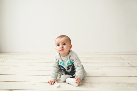 one of a kind: One year old cute baby boy sitting on rustic wooden floor over white