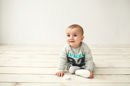 Un año de edad bebé lindo que se sienta en el piso de madera rústica sobre blanco Foto de archivo - 39343157