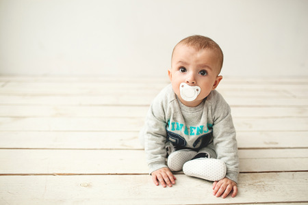 nipple: One year old cute baby boy sitting on rustic wooden floor over white